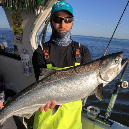 angler in rain pants from Mexico NY caught an impressive king salmon