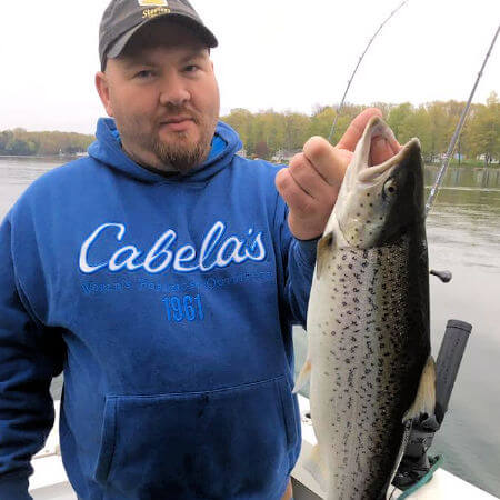 angler holds up a nice spring early season brown trout